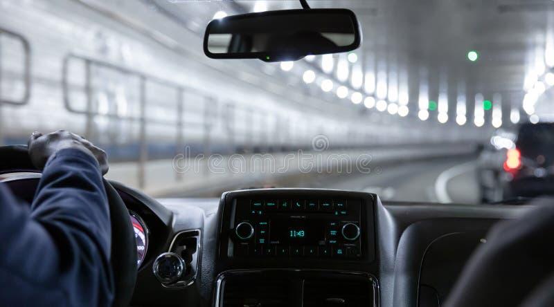 Conduzindo no túnel de Lincoln, New York Vista ascendente próxima na mão e no painel do motorista de táxi imagem de stock