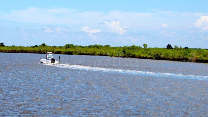 Conduzindo um barco abaixo do rio imagem de stock