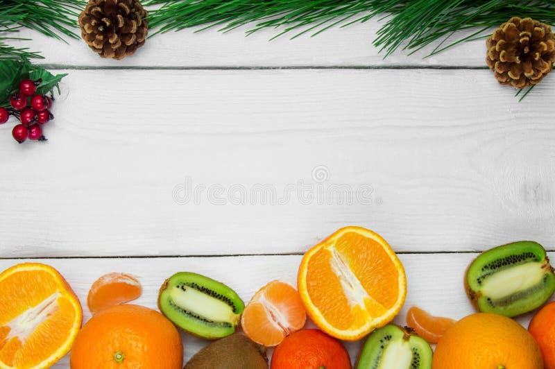 Cone da árvore de Natal da laranja, da tangerina e do ramo do fruto no fundo rústico de madeira branco fotos de stock royalty free