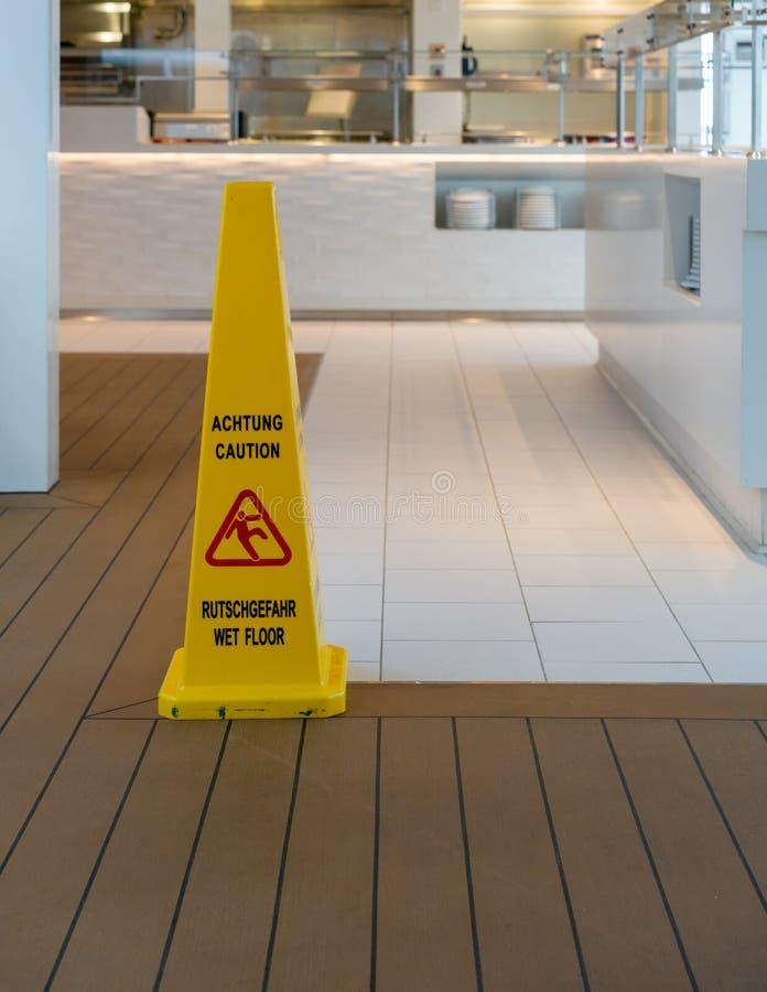 Cone de advertência amarelo para o assoalho molhado em inglês e em alemão fotos de stock royalty free