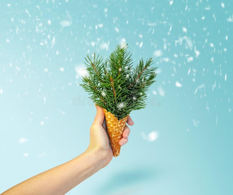 Cone de gelado de árvore de Natal na mão da mulher no fundo azul de Ligth Conceito do ano novo Composição mínima do feriado fotografia de stock royalty free