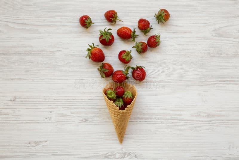 Cone de gelado doce do waffle com as morangos sobre o fundo de madeira branco, vista superior Configuração lisa, de cima de imagens de stock royalty free