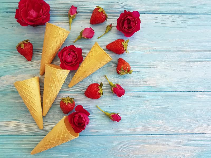 Cone for ice cream, strawberry, rose flower pattern on a blue wooden. Composition stock image