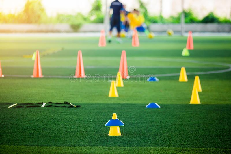 Cone markers is soccer training equipment on green artificial turf with blurry kid players training background. Material for training class of football academy stock images