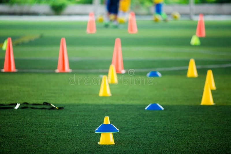 Cone markers is soccer training equipment on green artificial turf with blurry kid players training background. Material for training class of football academy stock photo