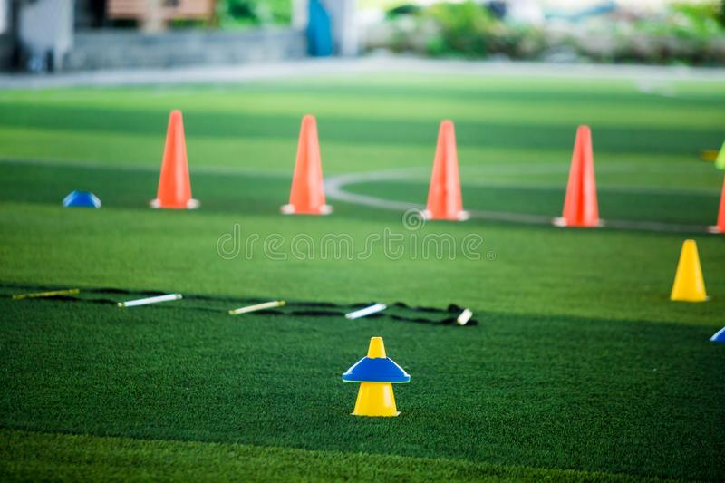 Cone markers is soccer training equipment on green artificial turf with blurry kid players training background. Material for training class of football academy stock photography