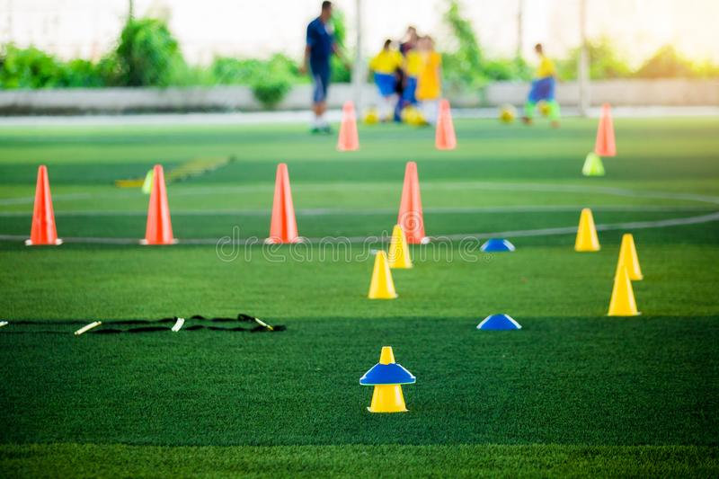 Cone markers is soccer training equipment on green artificial turf with blurry kid players training background. Material for training class of football academy royalty free stock photo