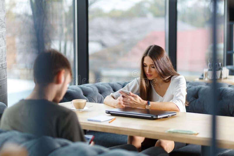 Conectado sempre, apego do Internet, jovem no café que olha seus smartphones imagens de stock