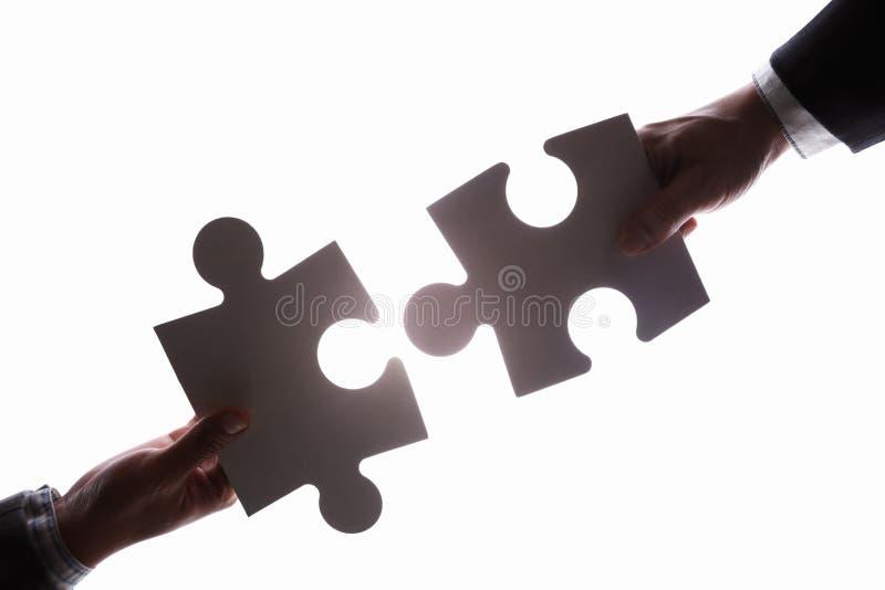Conectando duas partes do enigma do jigzaw imagens de stock