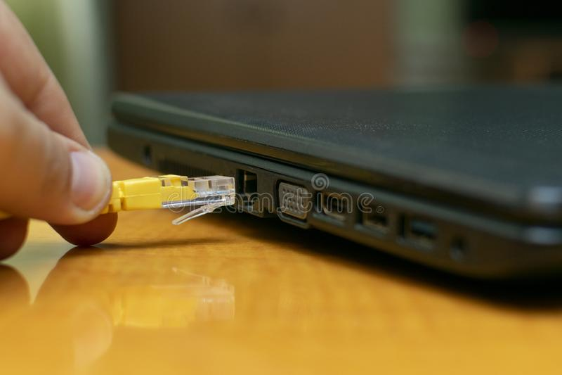 Conecte el cable de alambre de Internet con un ordenador portátil en fotografía de archivo
