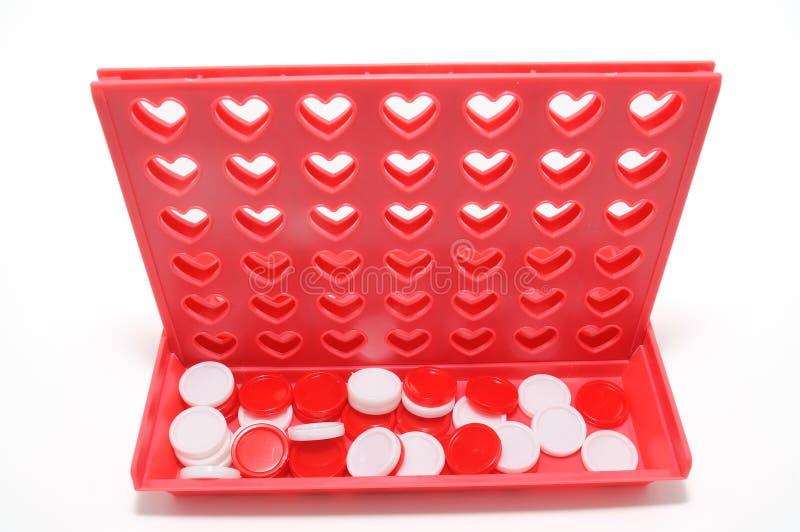 Conecte el juego cuatro con los agujeros en forma de corazón aislados en el fondo blanco. fotos de archivo