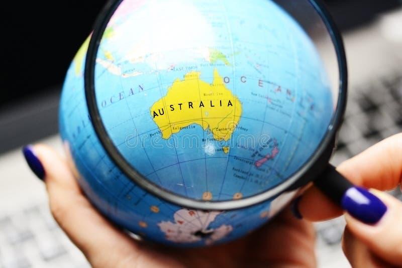 Conecte a tierra el globo del mundo con el foco en Australia debajo del vidrio de la lupa en mano de la mujer imagen de archivo libre de regalías