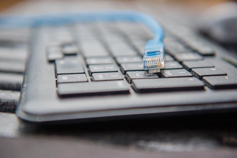 Conector da tomada do cabo ethernet no conceito da tecnologia do teclado do portátil do computador fotos de stock royalty free