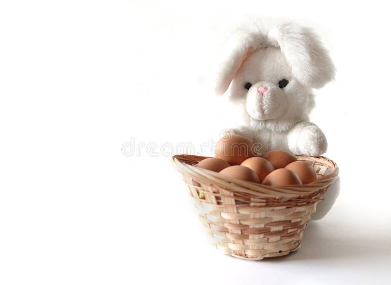 Conejito blanco del juguete con una cesta de huevos marrones imagen de archivo