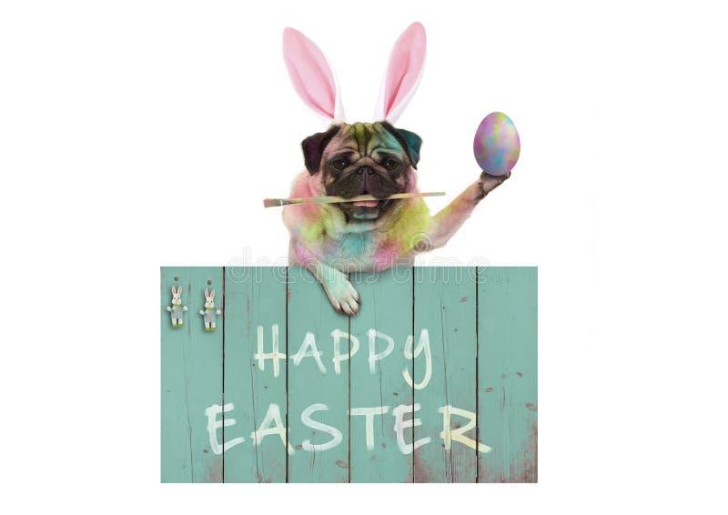 Conejito colorido del perro del barro amasado de pascua que pinta los huevos de Pascua con la brocha, colgando en muestra de made imagenes de archivo