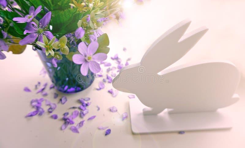 Conejito de pascua con las flores en un fondo blanco imagenes de archivo