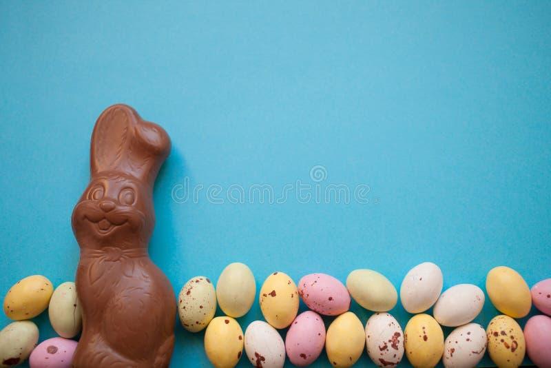 Conejito de pascua con los huevos coloridos presentados en fila en un fondo azul Copie el espacio imagen de archivo libre de regalías