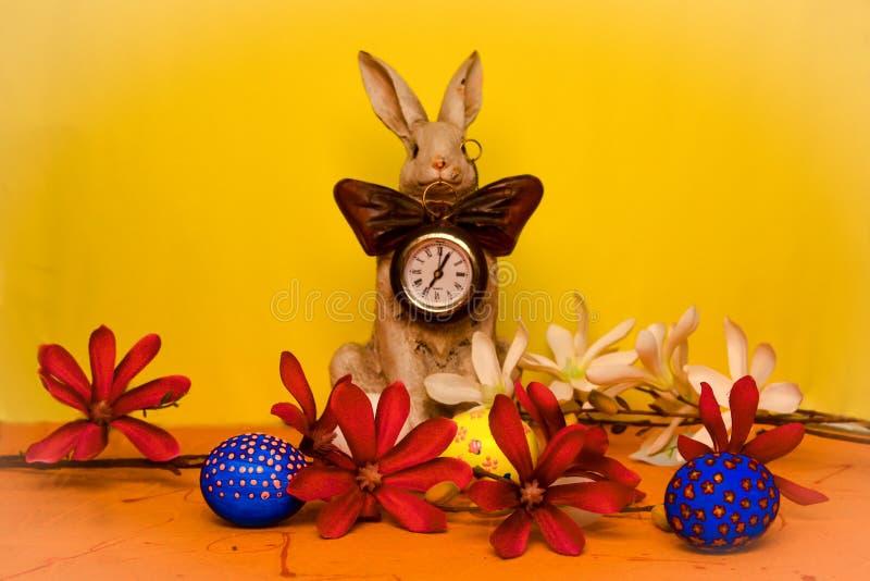 Conejito de pascua con un reloj en su pecho rodeado por las flores de la primavera con los huevos azules, amarillos y blancos imagen de archivo