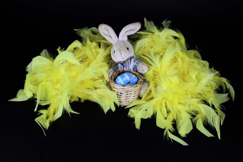 Conejito de pascua en plumas amarillas y el huevo pintado fotografía de archivo