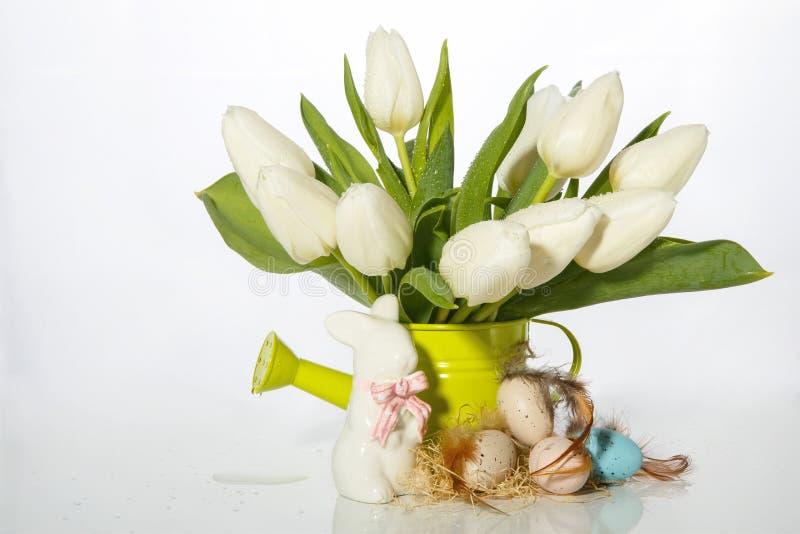 Conejito de Pascua fondo-Pascua y adornado con huevos de codornices y una regadera con los tulipanes fotos de archivo libres de regalías