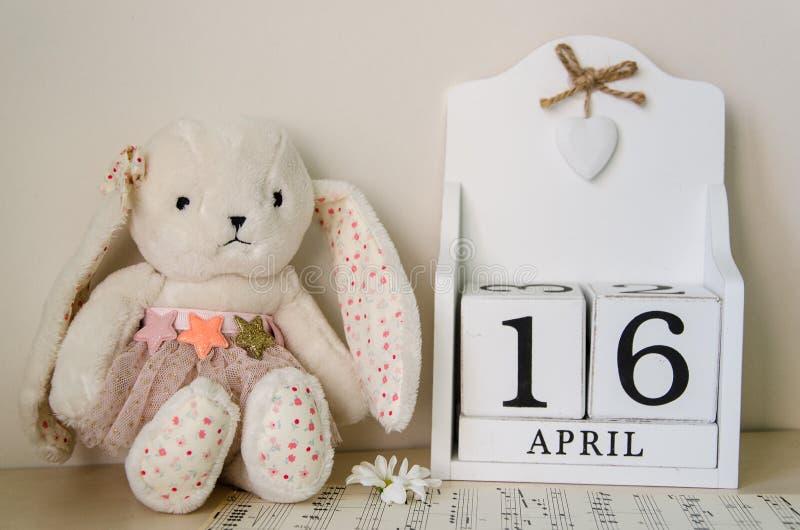 Conejito de pascua, huevos y calendario woodenPerpetual el fondo el 16 de abril de madera blanco pascua santa 2017 fotos de archivo libres de regalías
