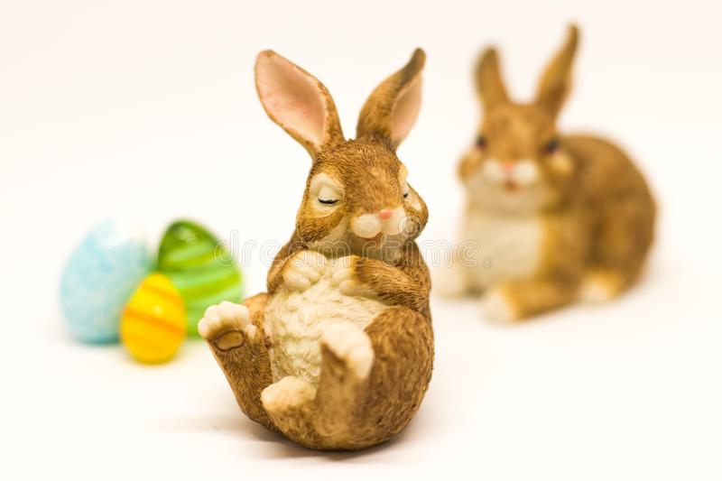 Conejito de pascua marrón soñoliento con los amigos y los huevos de cristal imagen de archivo libre de regalías