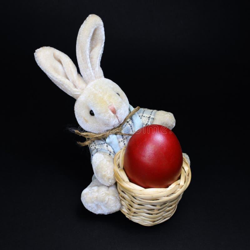 Conejito de pascua y huevo rojo pintado en cesta de madera fotografía de archivo