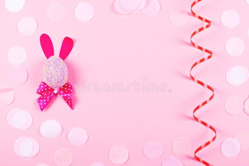 Conejito de pascua y serpentina en fondo rosado fotografía de archivo
