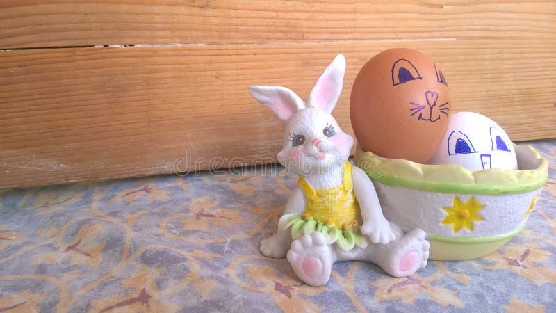 Conejito del juguete con la cesta y los huevos de Pascua imagenes de archivo