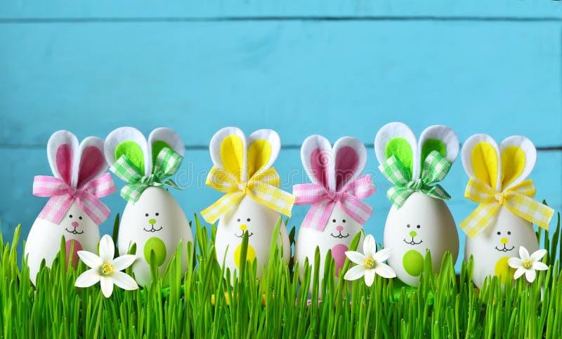 Conejito divertido de Pascua en hierba verde con los huevos y las flores de Pascua Fondo de Pascua fotos de archivo