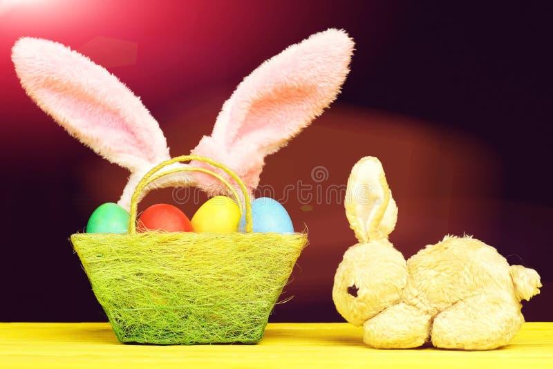 Conejito y cesta de Toy Easter por completo de huevos de Pascua coloreados fotos de archivo