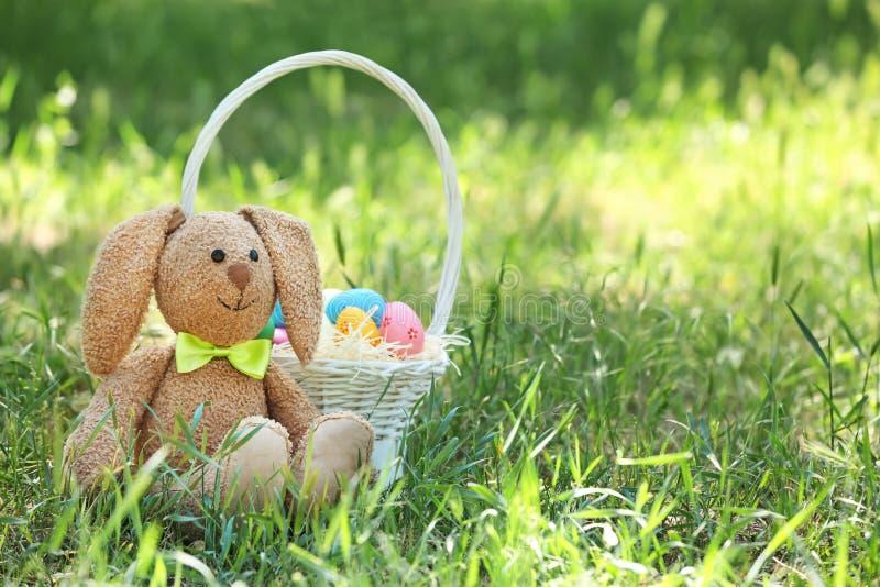 Conejito y cesta lindos del juguete con los huevos de Pascua en hierba imágenes de archivo libres de regalías