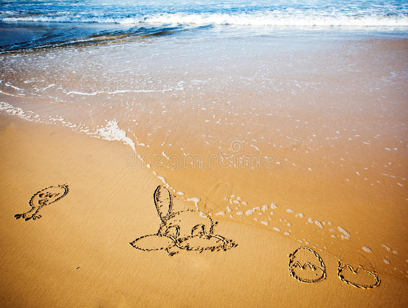Conejito y huevos de pascua en arena en la playa tropical fotografía de archivo libre de regalías