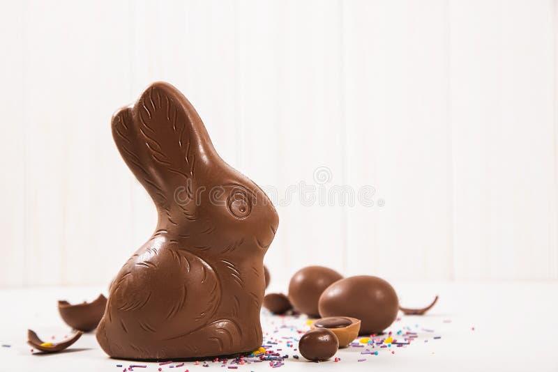 Conejito y huevos del chocolate de Pascua en el fondo blanco imagenes de archivo