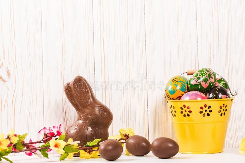 Conejito y huevos del chocolate de Pascua en el fondo de madera blanco fotografía de archivo libre de regalías