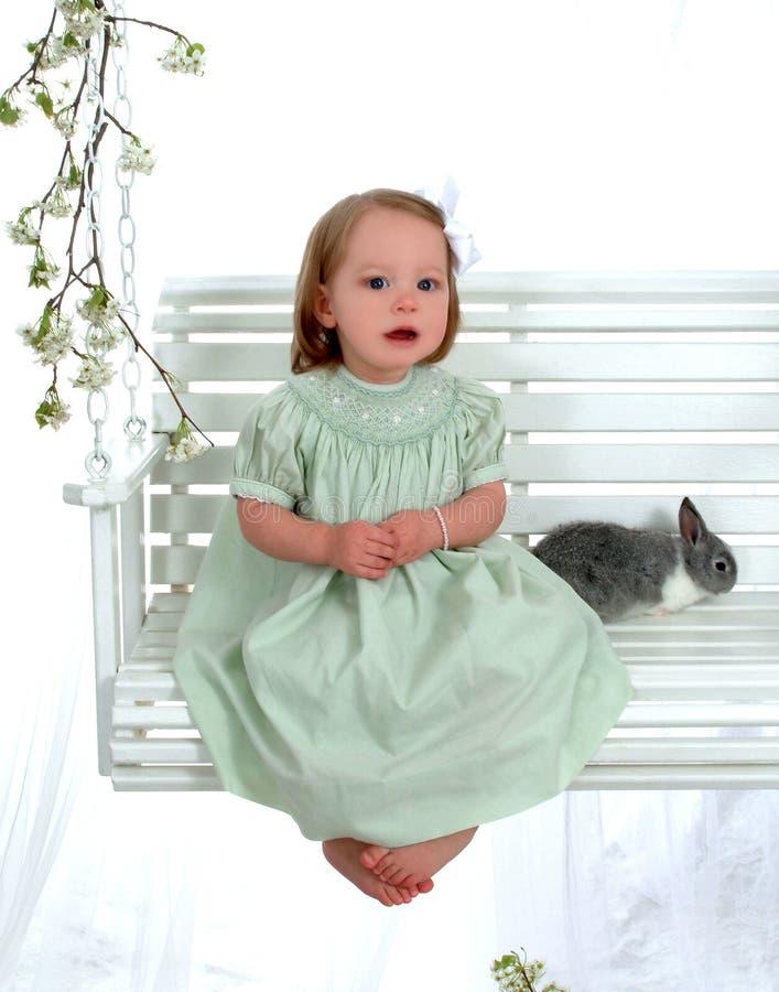 Conejito y muchacha en el oscilación foto de archivo libre de regalías