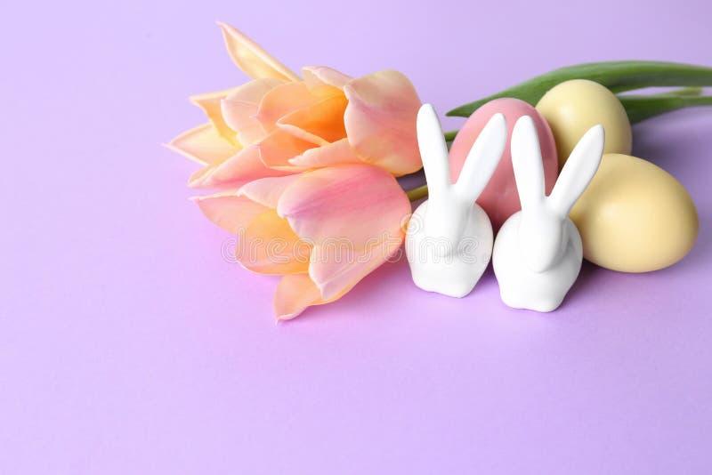 Conejitos de pascua de cerámica lindos, huevos teñidos y flores de la primavera fotografía de archivo libre de regalías