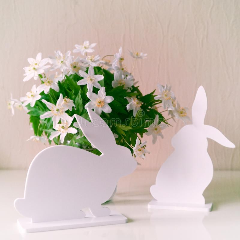 Conejitos de pascua con las flores de la primavera imagenes de archivo