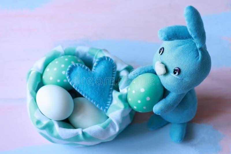 Conejo azul claro de Pascua cosido por las manos cerca de una cesta del pa?o con los huevos azul-blancos Trabajo hecho a mano Tar foto de archivo