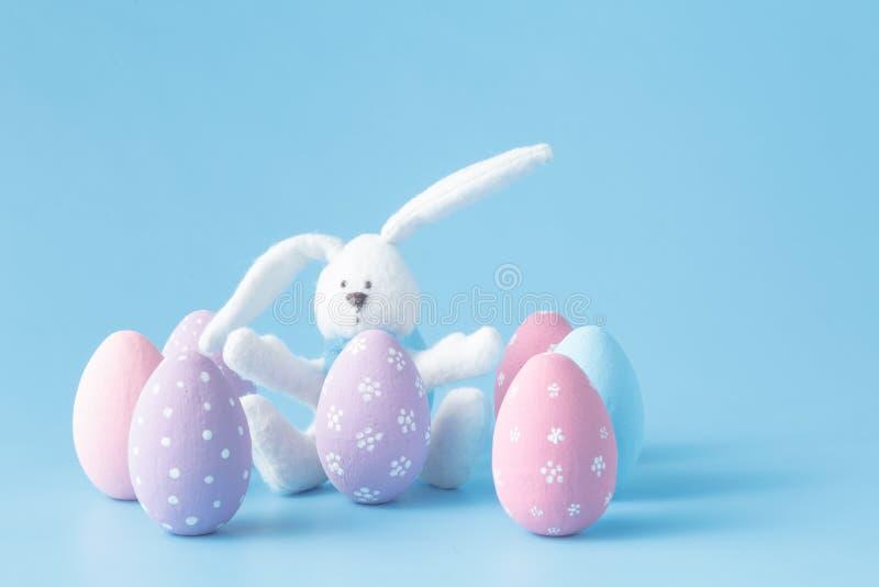Conejo con los huevos de Pascua en azul imagen de archivo