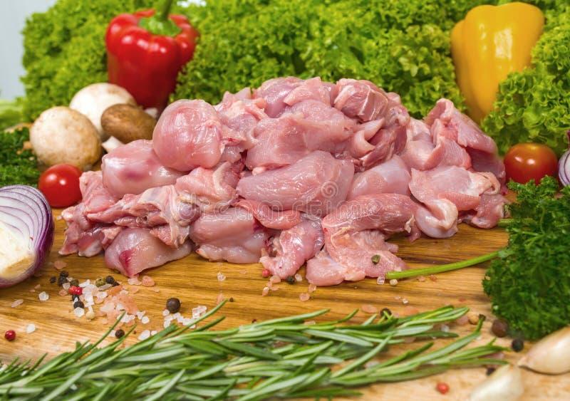 Conejo crudo de la cal en un fondo de madera con los tomates de cereza, hojas de la lechuga, ajo, pimienta de chiles, romero, ceb imagenes de archivo