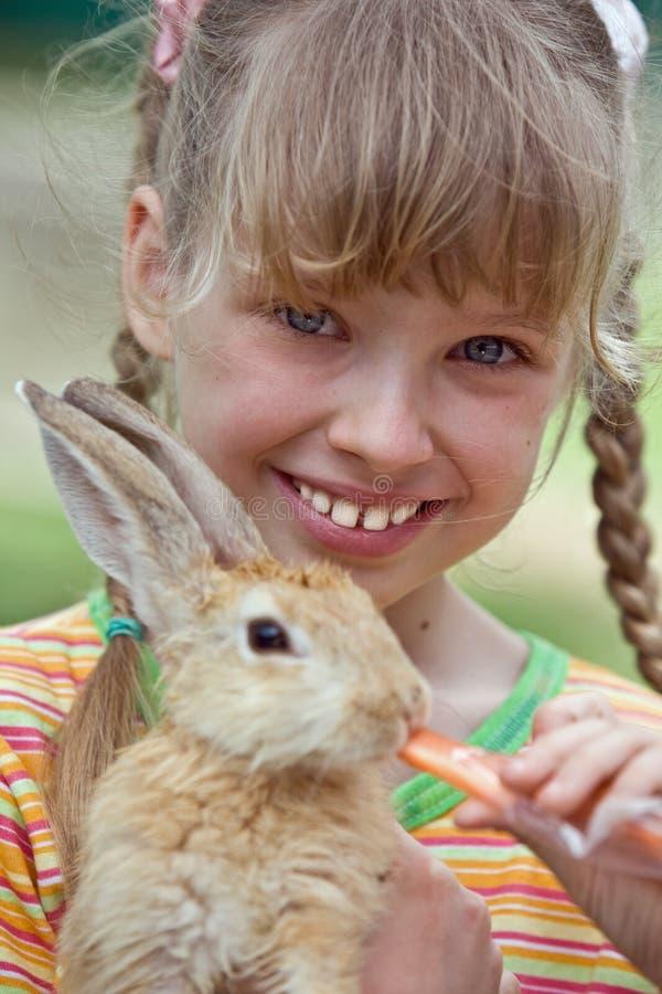 Conejo de la alimentación de la muchacha con la zanahoria. imágenes de archivo libres de regalías