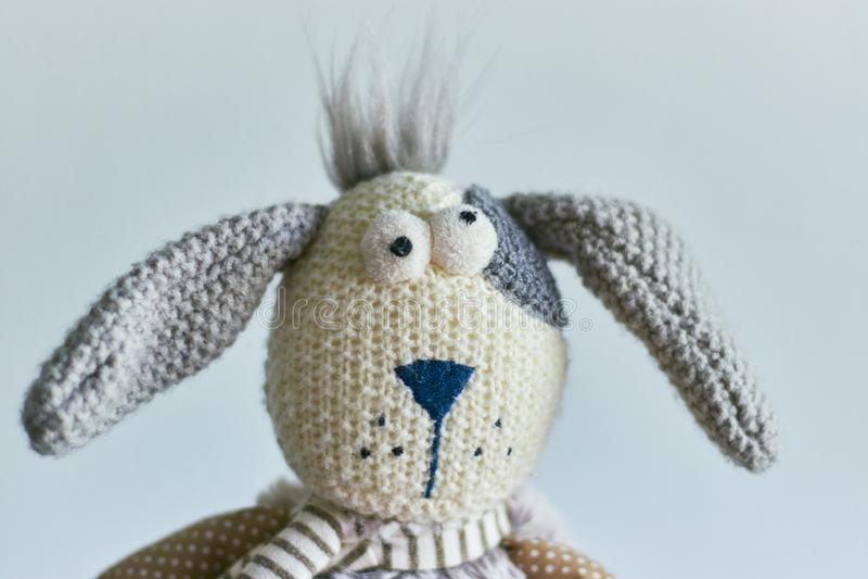 Conejo de la felpa del juguete de los ni?os aislado en un fondo ligero jefe de un cierre del conejo para arriba fotografía de archivo