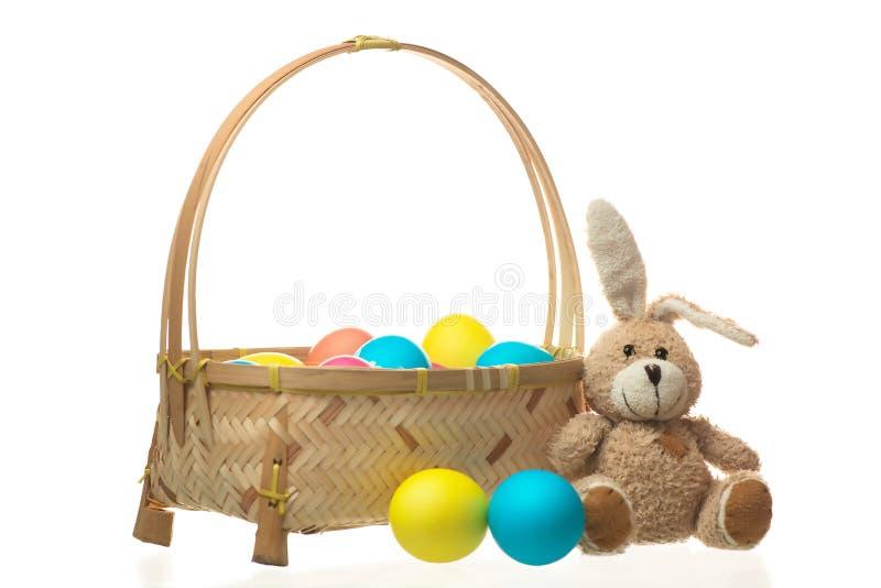 Conejo del peluche cerca de una cesta de huevos de Pascua coloridos aislados imagen de archivo