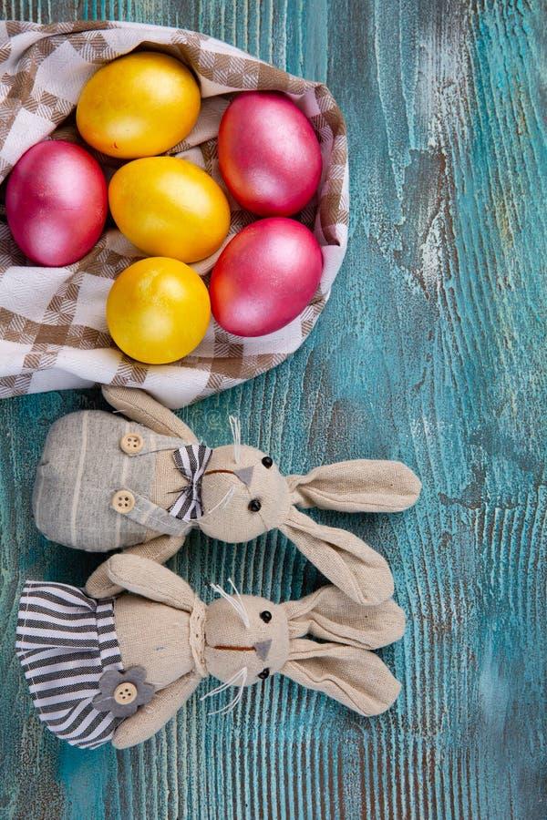 Conejos astutos mullidos con los huevos de Pascua en fondo de madera azul imagenes de archivo