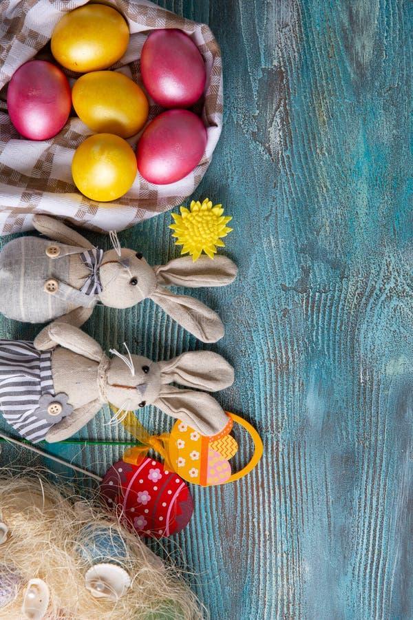 Conejos astutos mullidos con los huevos de Pascua en fondo de madera azul foto de archivo libre de regalías