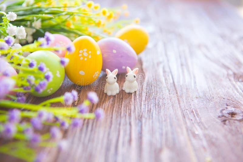Conejos con los huevos de Pascua en la tabla de madera Pequeño conejito de pascua lindo imágenes de archivo libres de regalías