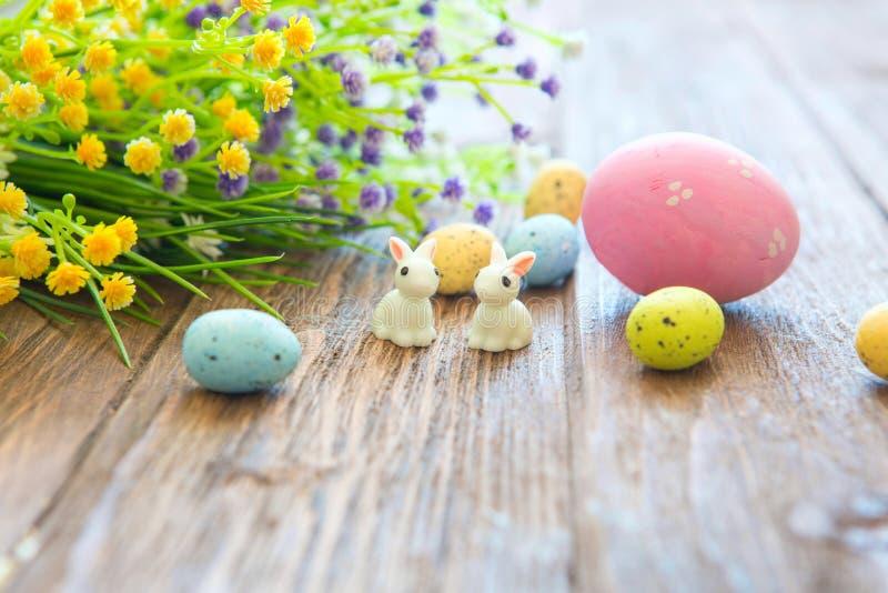 Conejos con los huevos de Pascua en la tabla de madera Pequeño conejito de pascua lindo imagen de archivo libre de regalías
