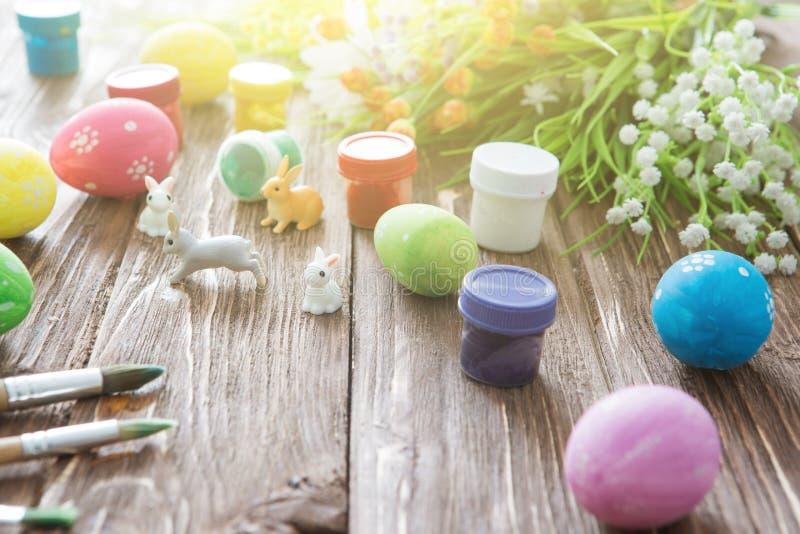 Conejos con los huevos de Pascua en la tabla de madera Pequeño conejito de pascua lindo foto de archivo libre de regalías