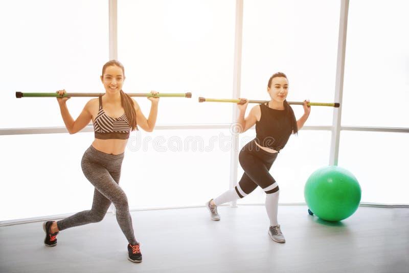 Conentrated młode kobiety ćwiczy w fintess izbowych Trzymają barbell na ramionach i kroki popierają kogoś Także modele zdjęcia royalty free